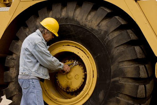 mechanic fixing a tire of large construction machinery